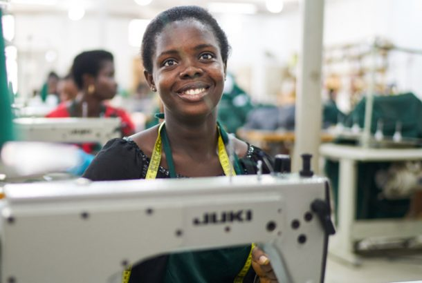 Woman at work in sewing factory, smiling with a tape measure around her neck